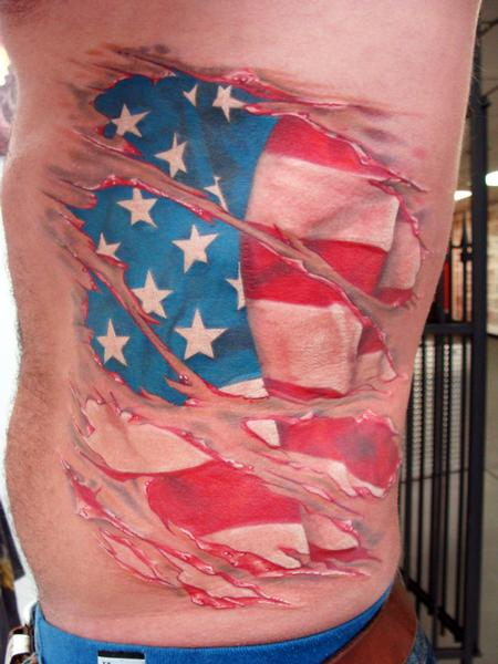 Large Tear Skin Patriotic Flag Tattoo On Ribs