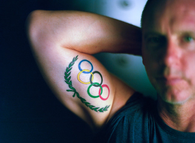 Man With Colorful Olympic Rings Tattoo On Muscles