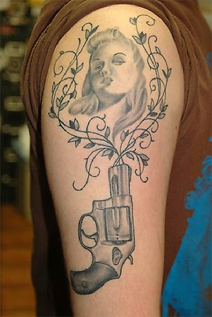 Marilyn Portrait And Short Pistol Tattoos On Arm