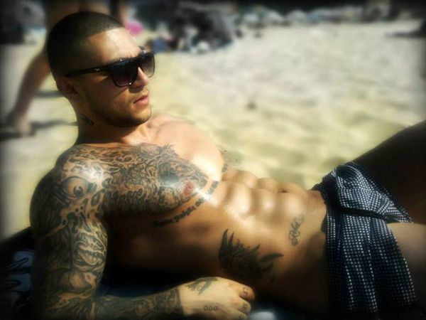 Muscular People With Tattoos On Beach