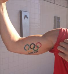 Olympian Rings And Roman Numerals Tattoos On Biceps