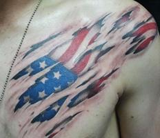 Patriotic Ripped Skin Tattoo On Chest To Shoulder