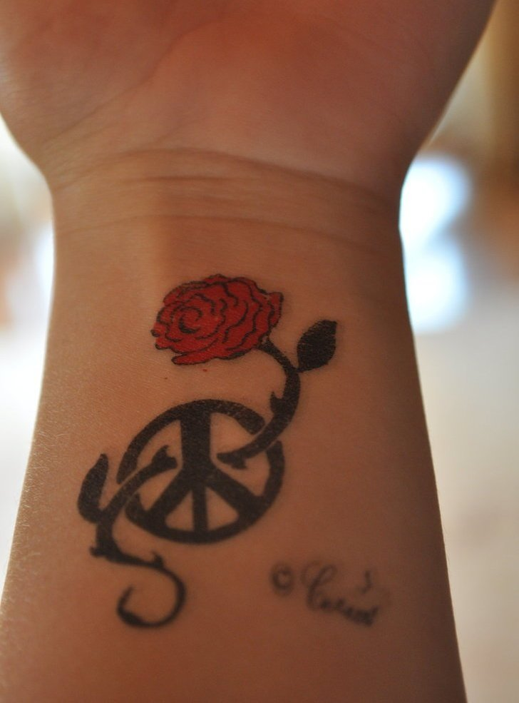 Red Rose And Black Peace Sign Tattoos On Wrist