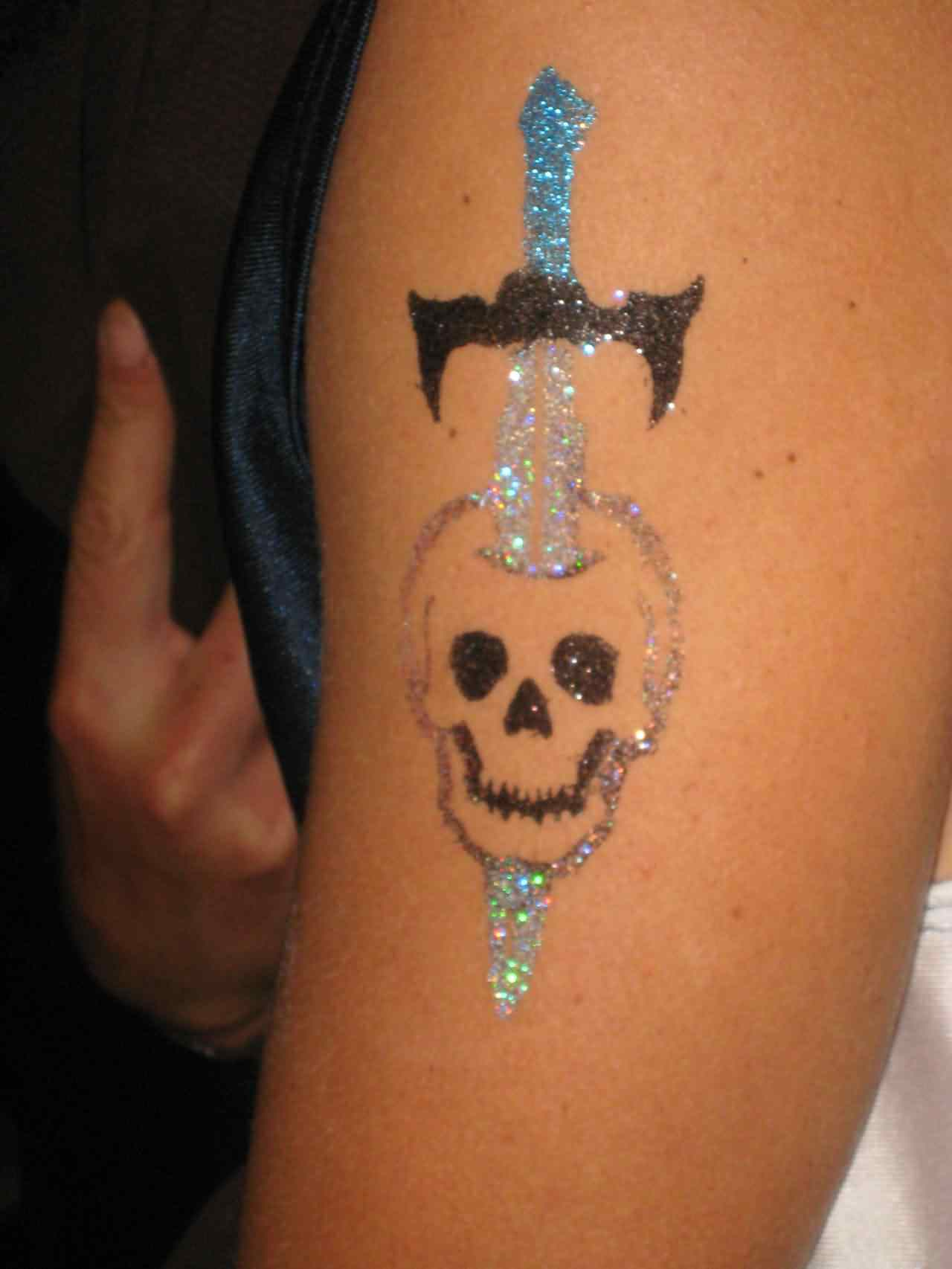 Glitter Sword In Skull Tattoo On Arm