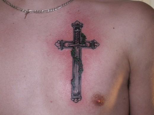 Sword In The Middle Of Cross Tattoo On Chest