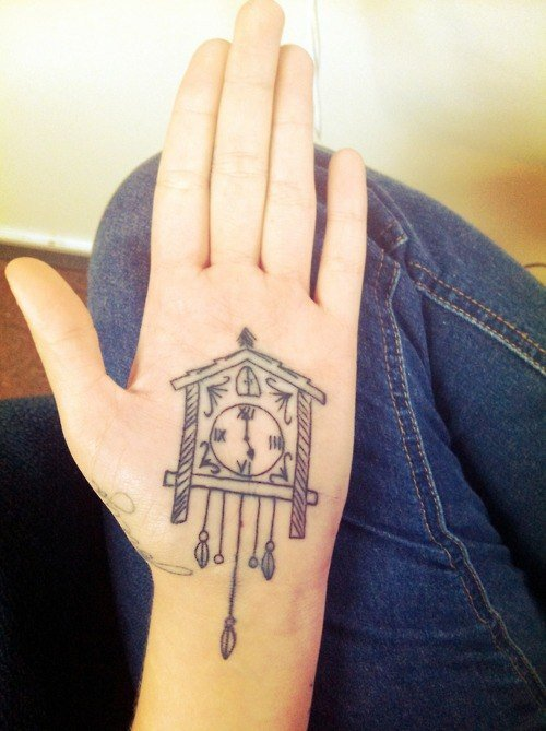 A Palm Tattoo Of A Cuckoo Clock That Stretches From The Palm Of The Hand To Wrist