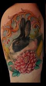 Amazing Rabbit And Flower Tattoo On Biceps