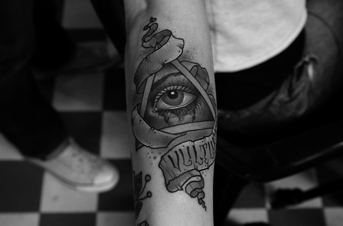 Banner And The Triangle Eye Tattoos On Arm