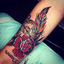 Beautiful Clock Feather And Rose Tattoos On Arm