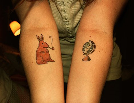 Brown Smoking Rabbit And Globe Tattoos On Forearms