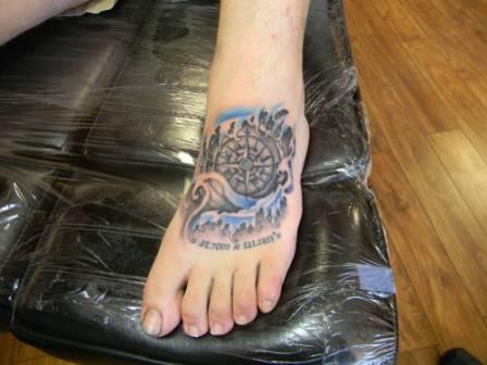 Compass In Blue Waves Tattoo On Foot