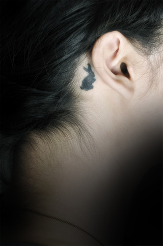 Cute Black Ink Rabbit Tattoo Behind Ear For Girls