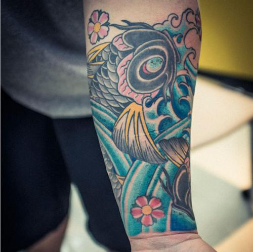 Forearm Covered With Blue Waves Flowers And A Black And Golden Koi Fish Tattoos