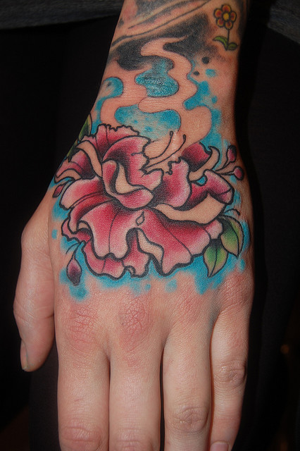Gorgeous Flower In Water Waves Tattoos On Hand