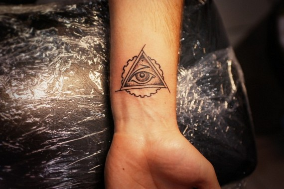Grey Ink Eye Triangle Tattoo On Inner Wrist