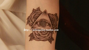 Grey Ink Eye Triangle Tattoo With Some Flowers On Arm