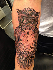 Grey Ink Owl Clock Tattoo On Forearm