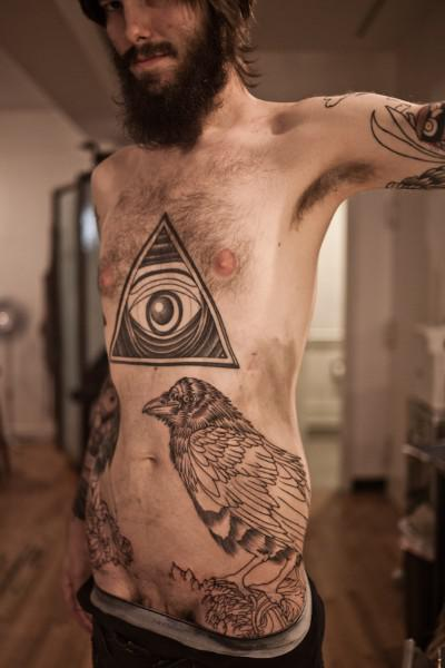 Man Has Triangle And Crow Tattoos