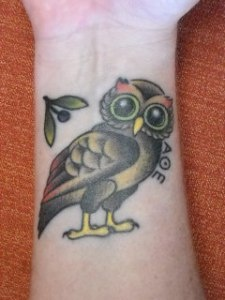 Owl With Yellow Claw Tattoo On Wrist