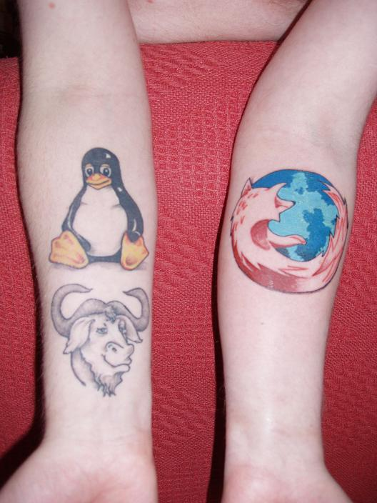 Penguin And Firefox Tattoos On Forearms