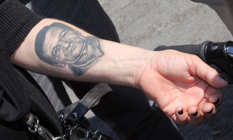 A Woman Shows A Tattoo Of Portrait On Forearm