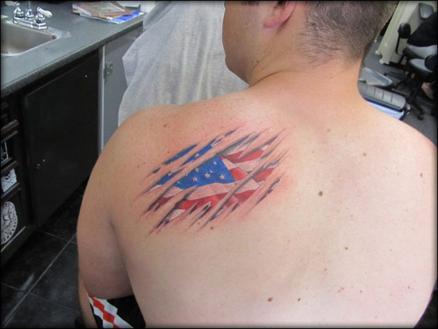 American Flag Ripped Skin Tattoo On Left Back Shoulder