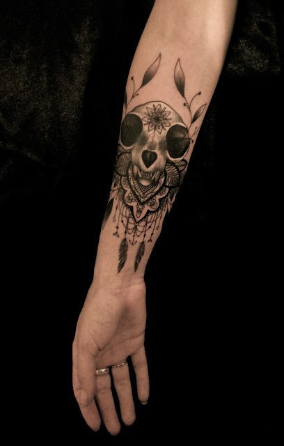 An Animal Skull With Lace Beads And Feathers Becomes A Feminine Tattoo On Lower Arm