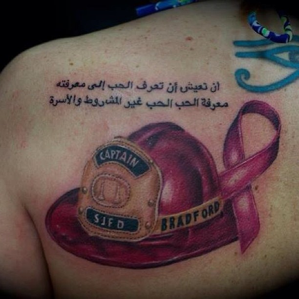 Arabic Lettering Pink Helmet And Cancer Ribbon Tattoos