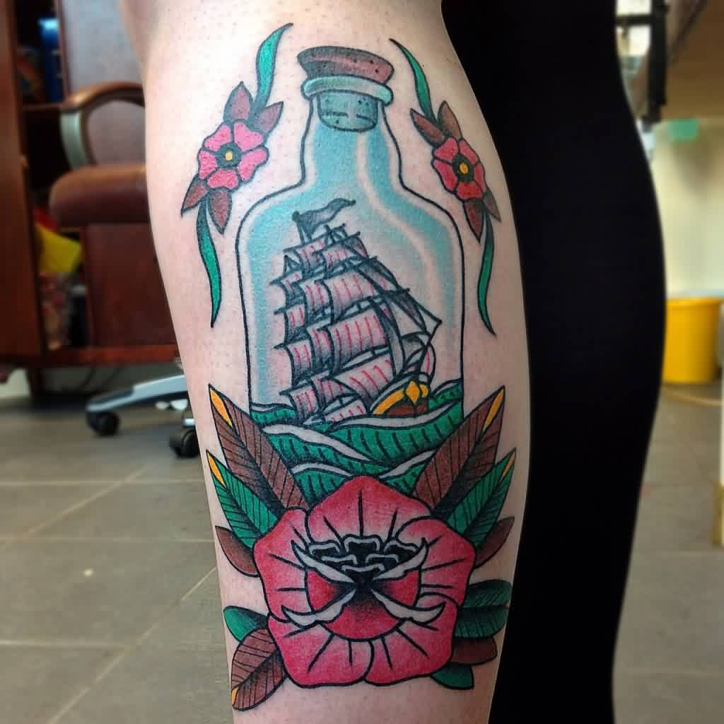 Beautiful Flowers And Ship Bottle Tattoos On Leg