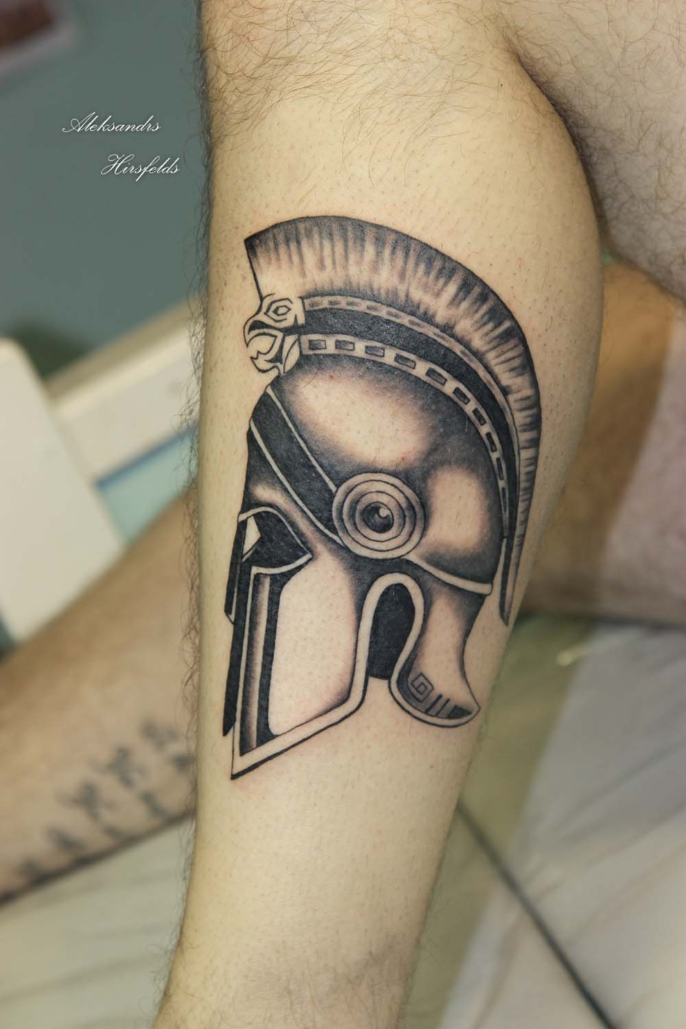 Black And Grey Ink Helmet Tattoo On Leg