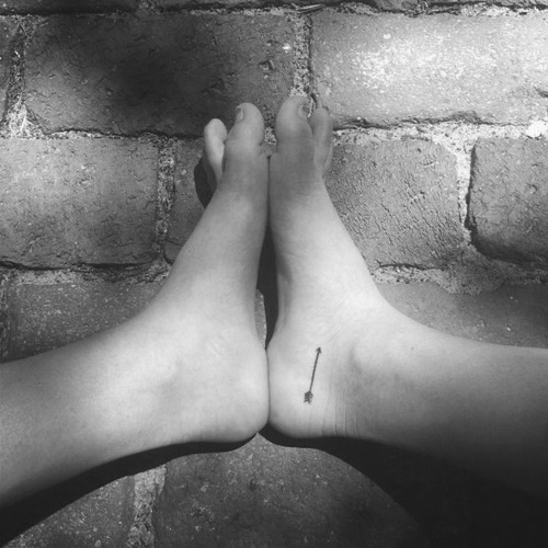 Black And White Thin Arrow Tattoo On Right Foot