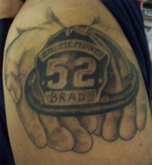 Black Firefighter Helmet In Hands Tattoo On Shoulder