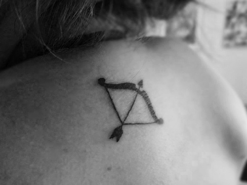 Black Ink Bow With Arrow Tattoo