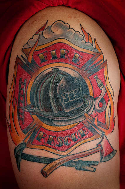 Black Ink Firefighter Helmet And Weapon Tattoos On Biceps