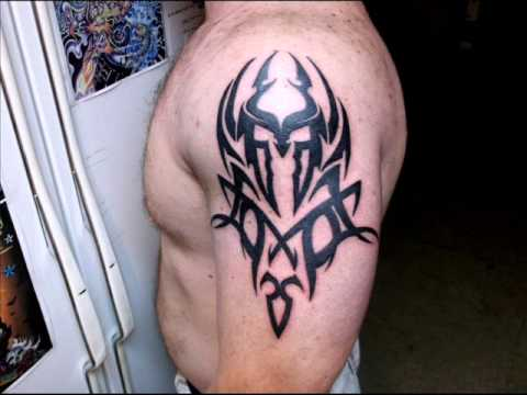 Black Ink Tribal Helmet Tattoo On Shoulder
