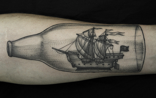 Bottle With Ship Tattoo On The Arm