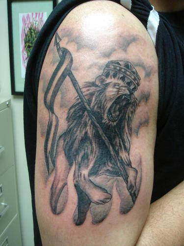 Clouds And Angry Lion With Flag Tattoo On Muscles
