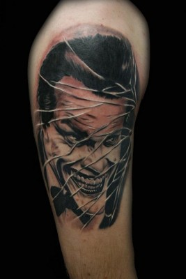 Cracked Glass Joker Portrait Tattoo On Biceps