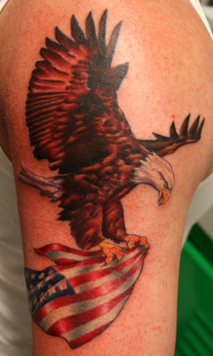 Eagle Carrying American Flag Tattoo On Biceps