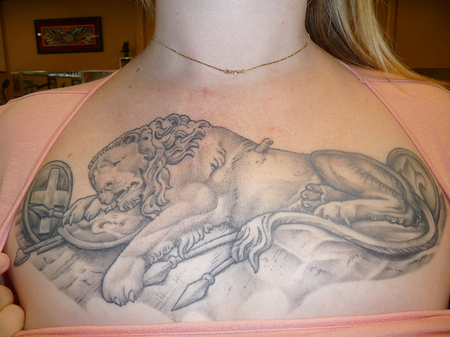 Female Shows Off Her Grey Animal Tattoo On Chest