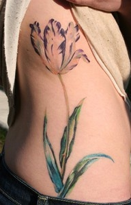 Female Shows Off Her Side Rib Tulip Tattoo
