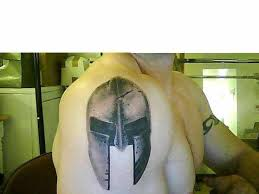 Grey And Black Ink Spartan Helmet Tattoo On Shoulder