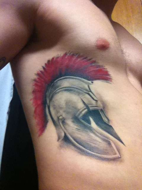 Grey Helmet With Red Hairs Tattoo On Ribs