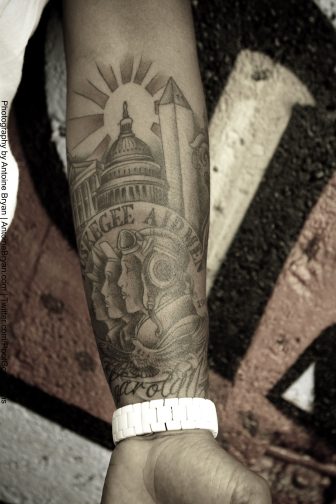 Grey Ink African American Tattoo On Lower Arm