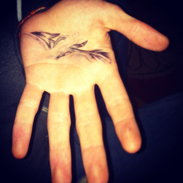 Grey Ink Arrow Through Palm Tattoo