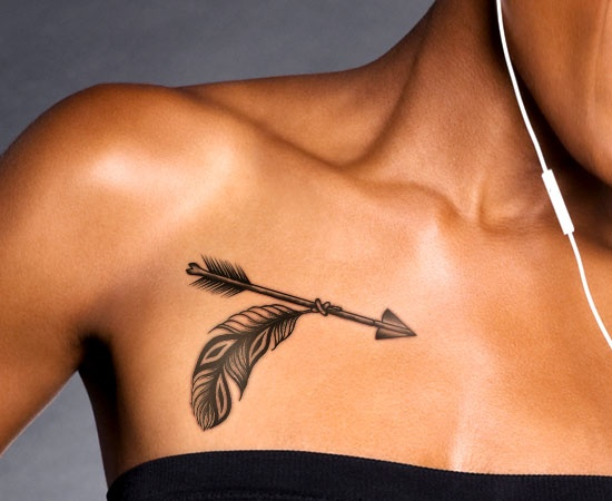 Grey Ink Arrow With Feather Tattoo Below Collarbone