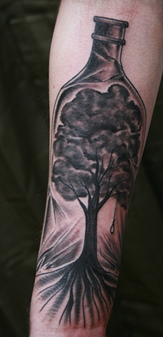 Grey Ink Bottle And Tree Tattoos On Arm