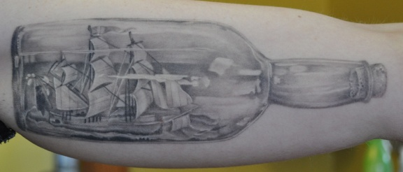 Grey Ink Bottle With Ship Tattoo On Arm