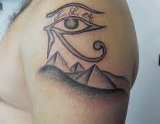 Grey Ink Egyptian Eye And Pryamid Tattoos On Shoulder