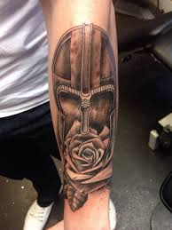 Grey Ink Helmet And Rose Tattoos On Lower Arm